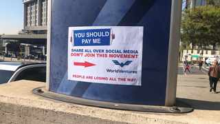 """WorldVentures representatives put up signs in Sandton this week with the words """"you should pay me"""", which is a spin on the company's campaign message of """"you should be here""""."""