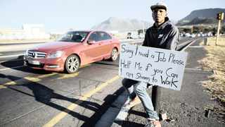 A man appeals for a job on the side of the road. File picture: Nic Bothma/EPA