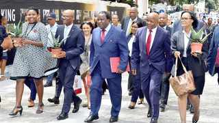 Finance Minister Tito Mboweni, flanked by deputy minister, Mondli Gungubele, right, and Treasury director-general, Dondo Mogajane, arrives in Parliament for his maiden Budget speech yesterday. Mogajane is holding an aloe that Mboweni said was an iconic plant, 'resilient, sturdy and drought resistant', adding that the country must take the bitter with the sweet to return to 'plum times'.     GCIS