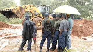 Police keep a close watch as a grader clears the road in Chimanimani, Zimbwabwe.  According to the government, cyclone Idai has killed more than 80 people, although residents say the figure could be higher.