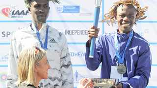Winner Stephen Mokoka receives the trophy from race ambassador Elana van Zyl-Meyer after the 2018 Cape Town Marathon. Photo: Ryan Wilkisky/BackpagePix
