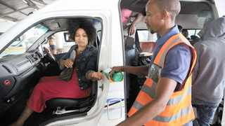 A passenger has sanitiser squirted on to her hands at a taxi at a Durban rank. Taxi operators have complained about the restriction placed on the number of people they can carry in taxis per trip.     Motshwari Mofokeng African News Agency (ANA)