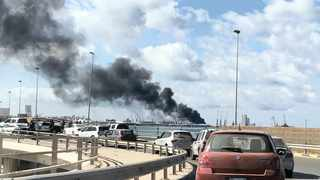 Smoke rises from a port of Tripoli after being attacked. South African military hardware exported to Turkey may end up in Libya or Syria, the writer says. File picture: Reuters