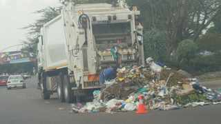 A refuse removal truck next to uncollected waste.