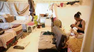 MOTHERLY LOVE: Gugu Nkabinde breast-feeds her baby daughter inside the communal section of the Fattis Mansion tent.   Picture: Denvor de Wee / Visual Buzz SA