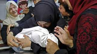 The mother of a Leila al-Ghandour holds her at the morgue of al-Shifa hospital in Gaza City. Picture: Thomas Coex/AFP