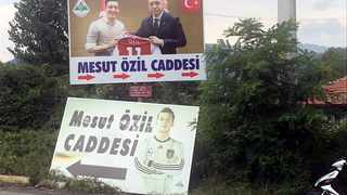 A billboard, serving as a street sign, with a picture of Arsenal's soccer player Mesut Ozil in the German national team kit is replaced by a picture of him with Turkish President Tayyip Erdogan in the Black Sea town of Devrek in Zonguldak, Turkey. DHA via Reuters