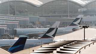 Tail fins of Cathay Pacific Airways Ltd. aircraft, center and right, are seen at Hong Kong International Airport in Hong Kong, China, on Saturday, March 11, 2018. Cathay Pacific is expected to report a full-year net loss of HK$2.7 billion ($345 million) for 2017, after a first-half deficit of HK$2.05 billion, according to the median estimate in a Bloomberg News survey of five analysts. Photographer: Anthony Kwan/Bloomberg