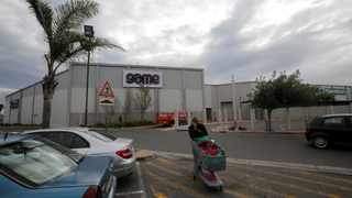 FILE PHOTO: A man walks past an outlet for Massmart-owned Game store in Cape Town