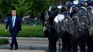 President Donald Trump walks past police in Lafayette Park after he visited outside St. John's Church across from the White House. Photo by: AP Photo/Patrick Semansky