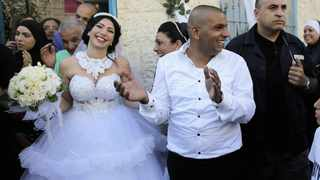 Groom Mahmoud Mansour (centre) and his bride Maral Malka celebrate with friends and family before their wedding in Mahmoud's family house in Jaffa, south of Tel Aviv. Picture: Ammar Awad