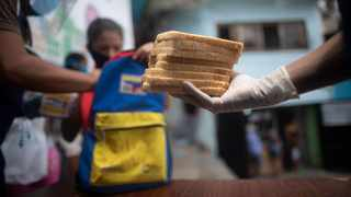 A volunteer holds out a stack of bread slices. Even though feeding 1 million South Africans one meal may not seem like much, for the millions of women, children and men facing food insecurity every day it could be the difference between life and death. Picture: AP