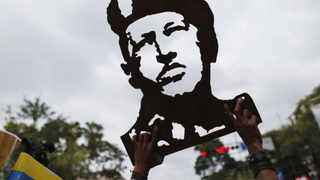 A supporter of Venezuelan President Hugo Chavez holds up a wooden handicraft carving of Chavez's face during a gathering outside Miraflores Palace in Caracas.