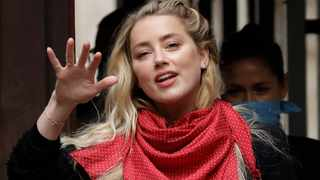 American actress Amber Heard waves at the media as she arrives at the High Court in London. Picture: Matt Dunham/AP