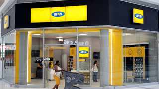 FILE PHOTO: A shopper walks past an MTN shop at mall in Johannesburg