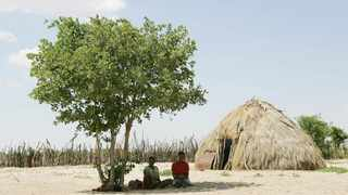 Two Basarwa women hide from the scorching sun in Metsiamenong, a remote village in the heart of the Central Kalahari Game Reserve, a place popular with tourists visiting Botswana. Picture: AP