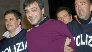 Italian police officers celebrate as they escort Antonio Iovine, one of the most powerful leaders of the Camorra organised crime group, after his arrest in Naples in 2010. File photo: AFP