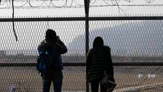 Visitors take their souvenir pictures in front of a barbed-wire fence at the Imjingak Pavilion near the border village of Panmunjom, which has separated the two Koreas since the Korean War, in Paju, north of Seoul, South Korea, Wednesday, March 6, 2013. North Korea's military is vowing to cancel the 1953 cease-fire that ended the Korean War, straining already frayed ties between Washington and Pyongyang as the United Nations moves to impose punishing sanctions over the North's recent nuclear test. (AP Photo/Lee Jin-man)