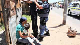 Cape Town. 131230. Manenberg residents had their streets thoroughly walked through by Police and Metro Police today. Random searches were conducted on passes by. A young child and her mother watches as a man is randomly searched in full view. Reporter Caryn Dolley. Picture COURTNEY AFRICA