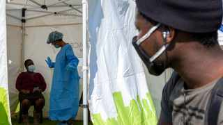 A man looks on through an opening of a tent as a woman watches the health worker explains the process of collecting a sample for coronavirus testing. File picture: Themba Hadebe/AP