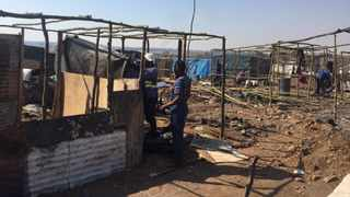 People rebuild after a wild fire torched over 79 shacks at Plastic View in the east of Pretoria. Picture: James Mahlokwane