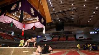 Sumo wrestlers fight on the ring as spectators' seats are empty during the Spring Grand Sumo Tournament in Osaka, western Japan on Sunday. The 15-day sumo tournament started on Sunday with no spectators, affected by fears of the new coronavirus outbreak. Photo: AP