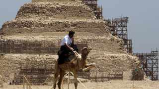 A policeman guards the site of the step pyramid of Saqqara about 30 km (19 miles) south of Cairo, May 23, 2011. Egypt's Minister of State for Antiquities Zahi Hawass opened six tombs at the site to tourists for the first time. Of the six, the tomb of Maya, who was the treasurer of King Tut, and the tomb of King Tut's general Horemheb, who also later became king, are considered the most important. REUTERS/Asmaa Waguih (EGYPT - Tags: TRAVEL SOCIETY ANIMALS CRIME LAW)