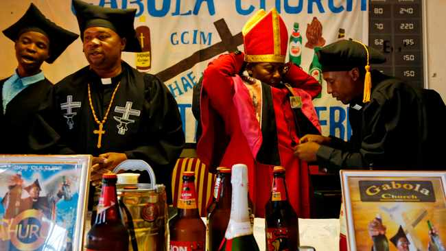 The leader of the Gabola Church, self-proclaimed Pope Tsietsi Makiti, second from right, prepares for a service in a bar in Orange Farm, south of Johannesburg. Picture: Denis Farrell/AP