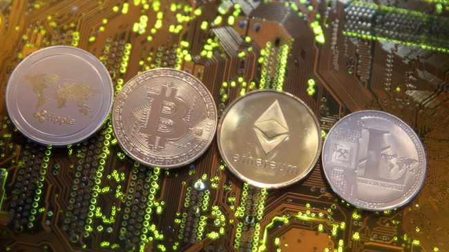 Representations of the Ripple, Bitcoin, Etherum and Litecoin virtual currencies are seen on a motherboard in this illustration picture. Photo: Reuters.