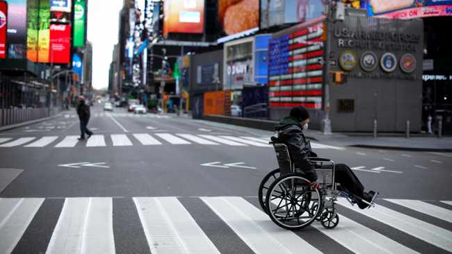 Man in wheelchair crosses nearly empty 7th Avenue in Times Square in Manhattan during the outbreak of the coronavirus disease (COVID-19) in New York