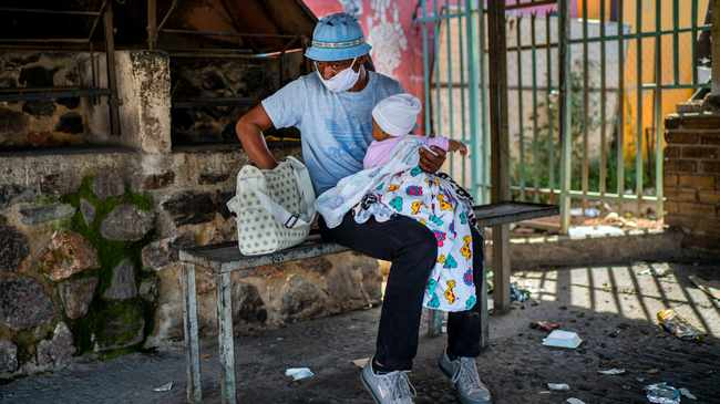 Stanley takes care of his 10-month-old daughter Ntokoso as his wife lined up to receive food parcels in the Olievenhoutbos township. Picture: Jerome Delay/AP