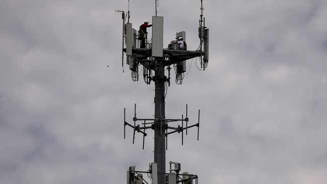 Workers install 5G telecommunications equipment on a T-Mobile tower in Seabrook, Texas. Picture: Reuters/Adrees Latif