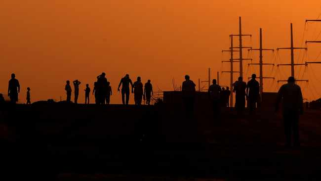 Workers on a highway construction site return after day's work. The interesting development in the last two or so years is what appears to be a conscious attempt to 'rigiditize' wage structure in the South African economy. Photo: Manish Swarup/AP