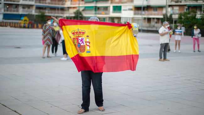 A woman holds a Spanish flag during a protest against the Spanish government amid the lockdown to prevent the spread of coronavirus in Alcorcon. The Spanish government is allowing Madrid and Barcelona to ease their lockdown measures, which were introduced to fight the coronavirus pandemic. Photo: Manu Fernandez/AP
