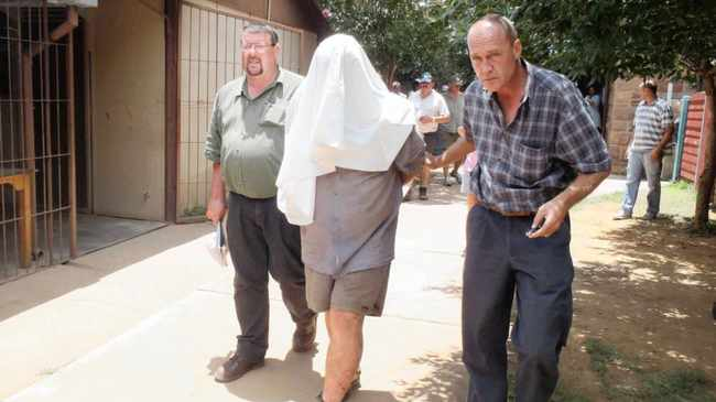 11.01.2012 Johan Kotze is escorted by police from the cells at Modimolle police station to an awaiting car to be taken to a clinic to receive treatment for his injuries. Picture: Graeme Hosken