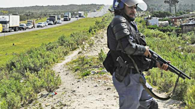 Cape Town 140915- Police officer standing next to the N2 during a srvice delivery protest in Grabow. Picture Cindy waxa.Reporter Murray/Argus