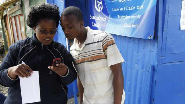 A Standard Bank employee shows a newly signed client how to use cellphone banking as part of a drive to take banking to poorer areas in Cape Town's Khayelitsha township. The lender's mobile transactions are already growing more than 50 percent a year. File photo: Reuters