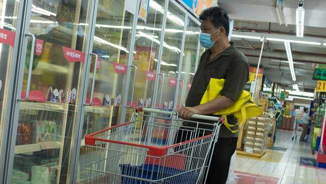A man looks at frozen food products in a supermarket in Beijing, China. Picture: Thomas Peter/Reuters