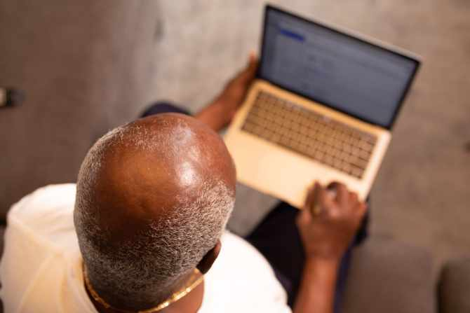 A bald man sitting on his computer. Image: Pexels